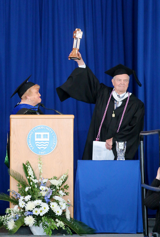 ". Jonathan Tressler � The News-Herald <br> John F. Platz, one of Lakeland Community College\'s charter faculty members, a former Wickliffe City Council member and former Lake County Commissioner who served six terms raises the Distinguished Service Award presented to him by Kathleen ""Kay\"" Malec, at left, during the 50th Annual Lakeland Commencement May 13."