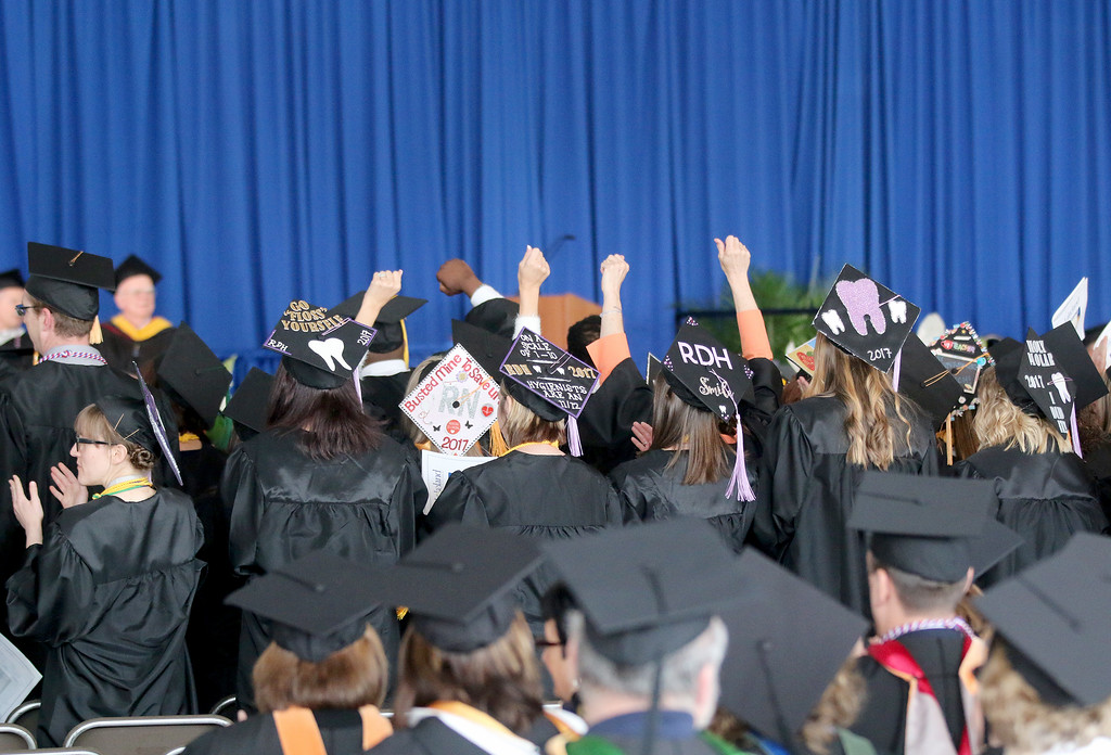 . Jonathan Tressler � The News-Herald <br> Lakeland Community College graduates give a sign of solidarity as their contemporaries are recognized during the school\'s 50th Annual Commencement May 13.