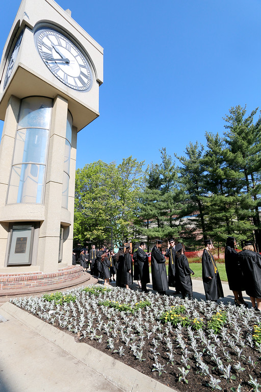 . Jonathan Tressler � The News-Herald <br> The line of soon-to-be Lakeland Community College graduates snakes past the school\'s characteristic clock tower May 13 shortly before the school\'s 50th Annual Commencement commences.