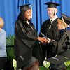 """Jonathan Tressler — The News-Herald <br> Lakeland Community College Board of Trustees Chairwoman Kathleen """"Kay"""" Malec shakes hands with one of the school's most recent graduates May 13 during Lakeland's 50th Annual Commencement at its Main Campus in Kirtland as fellow board member Kenneth Quiggle smiles in the background."""