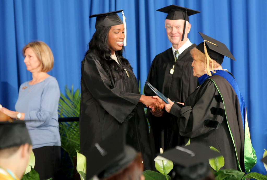 ". Jonathan Tressler � The News-Herald <br> Lakeland Community College Board of Trustees Chairwoman Kathleen ""Kay\"" Malec shakes hands with one of the school\'s most recent graduates May 13 during Lakeland\'s 50th Annual Commencement at its Main Campus in Kirtland as fellow board member Kenneth Quiggle smiles in the background."