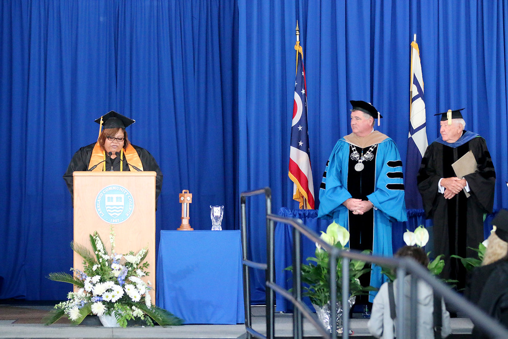 . Jonathan Tressler � The News-Herald <br> At left, Tiffany Jackson, a graduate of Lakeland Community College who earned an associate of applied sciences degree in human services addresses the crowd at the school\'s 50th Annual Commencement May 13 as college President Morris Beverage, center, and the school\'s first President, Wayne Rodehorst, look on.