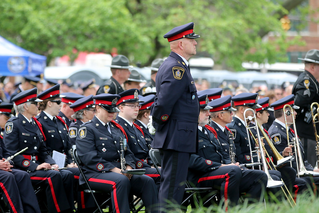 . Jonathan Tressler � The News-Herald <br> An officer from the Waterloo Regional Police in Ontario, Canada, stands at ease during the conclusion of the Greater Cleveland Peace Officers Memorial Parade and Memorial Service in Downtown Cleveland May 19 as the agency\'s band is seated behind him.