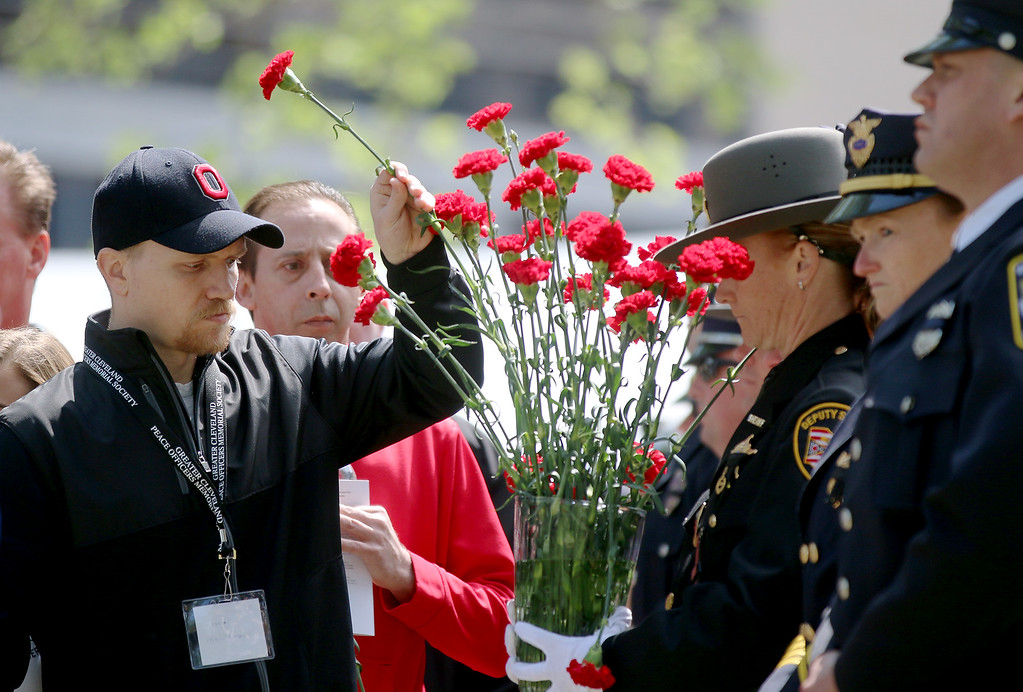 . Jonathan Tressler � The News-Herald <br> Family and friends of fallen police officers place roses in honor of their loved ones May 19 during the 32nd Annual Greater Cleveland Peace Officers Memorial Parade and Memorial Service in Downtown Cleveland.