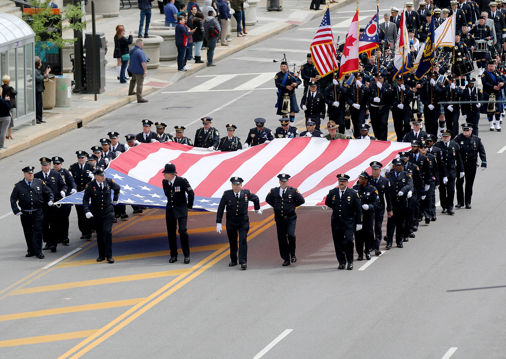 . Jonathan Tressler � The News-Herald <br> Officers from a variety of public safety agencies carry a huge American Flag down Lakeside Avenue towards the Greater Cleveland Peace Officers Memorial at Huntington Park May 19 during the 32nd Annual Annual Greater Cleveland Peace Officers Memorial Parade and Memorial Service in Downtown Cleveland.