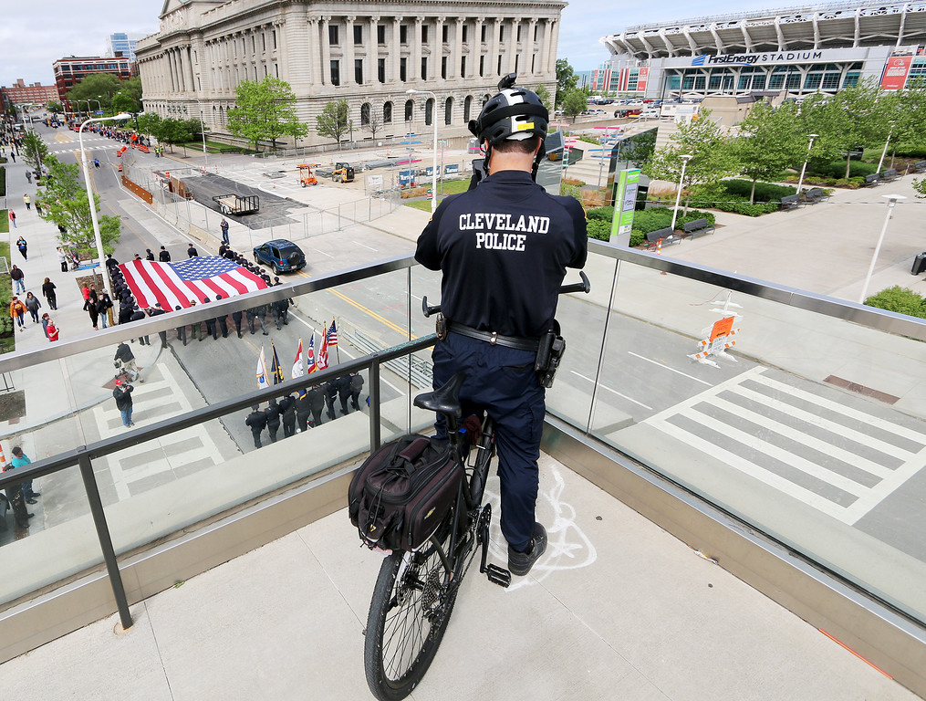 . Jonathan Tressler � The News-Herald <br> A Cleveland Police Department Officer on bicycle detail snaps a mobile-phone photo from above the convention center as the big flag passes beneath on Lakeside Avenue during the 32nd Annual Greater Cleveland Peace Officers Memorial Parade and Memorial Service in Downtown Cleveland May 19.