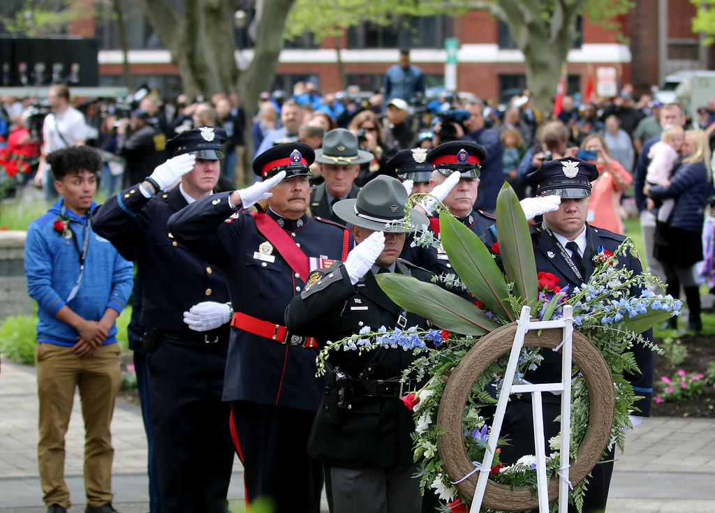 . Jonathan Tressler � The News-Herald <br> An honor guard consisting of Ohio Highway Patrol troopers, Canadian law enforcement officers, Cleveland police and others salute during a wreath-presentation movement honoring fallen Ohio Highway Patrol Trooper Kenneth Velez during the Cleveland Police Memorial service May 19. At far left is Velez\'s son, Christian Lorenzo Velez.