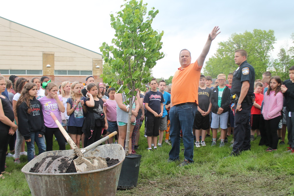. Kristi Garabrandt � The News-Herald <br> Willowick D.A.R.E Officer, Don Slapnicker and the fifth grade class from Royalview Elementary School look on as Willowick Mayor Rich Regovich explains how a tree planted in their honor as part of a long standing tradition will help make the part look nicer.