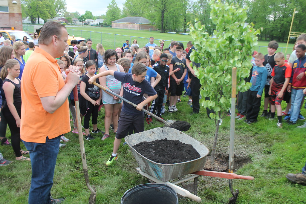 . Kristi Garabrandt � The News-Herald <br> Willowick Mayor Rich Regovich and the fifth grade class from Royalview Elementary School look on while classmate Kenny Neal puts dirt around the tree planted in Manry Park on May 22,  in honor of the class.