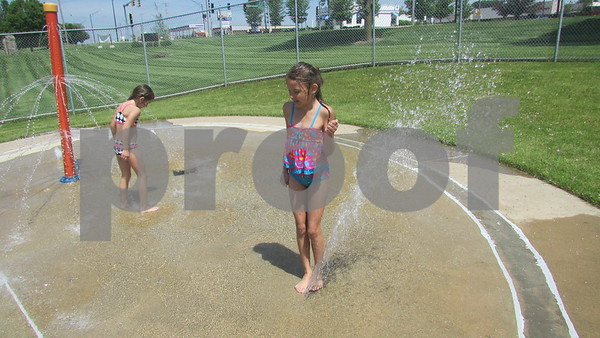 Chloe Domroes, 7, plays on the splash pad Saturday with her sister, Courtney, 6, at Hopkins Park Pool in DeKalb.