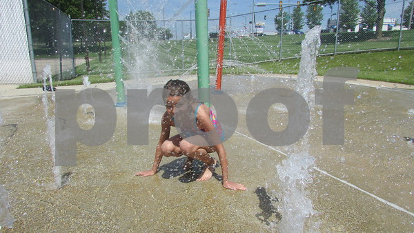 Chloe Domroes, 7, plays on the splash pad Saturday at Hopkin's Park Pool in DeKalb.