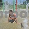 Chloe Domroes, 7, plays on the splash pad Saturday at Hopkin's Park Pool in DeKalb.