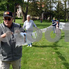 Tom Harris and others from the DeKalb Interfaith Network For Peace and Justice, lead a line of remembrance photos to the Memorial Day festivities on Monday at The Ellwood House Museum.  Steve Bittinger - For Shaw Media