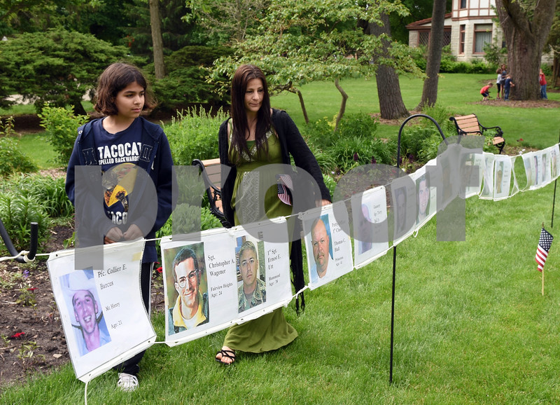 Imtihaan Hardy, 11, and Qiana Hardy of DeKalb look over a long line of remembrance photos of Illinois servicemen killed in action in recent wars. The photos were part of the DeKalb Memorial Day program at The Ellwood House Museum on Monday.  Steve Bittinger - For Shaw Media