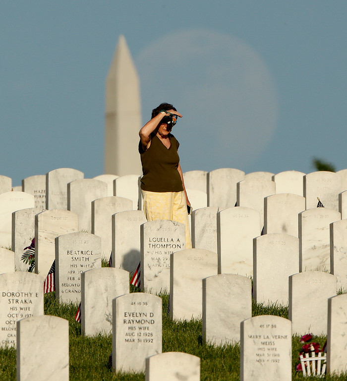 . Carol Page, from Leavenworth, Kan., looks for her parents\' graves as the moon rises in the distance at Leavenworth National Cemetery on the eve of Memorial Day, Sunday, May 27, 2018, in Leavenworth, Kan. (AP Photo/Charlie Riedel)