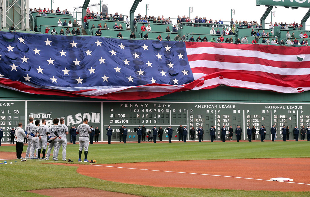 . A United States flag is unfurled over the Green Monster at Fenway Park in honor of Memorial Day before a baseball game between the Boston Red Sox and the Toronto Blue Jays, Monday, May 28, 2018, in Boston. (AP Photo/Elise Amendola)