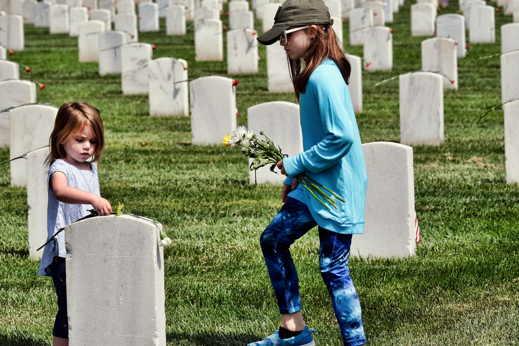 . Zoey Borquez, 3, left, and her sister Emma, 10, place flowers on veterans gravestones during an observance for Memorial Day at the Los Angeles National Cemetery in Los Angeles on Monday, May 28, 2018. Californians are paying their respects on Memorial Day to those who have died serving their country. (AP Photo/Richard Vogel)