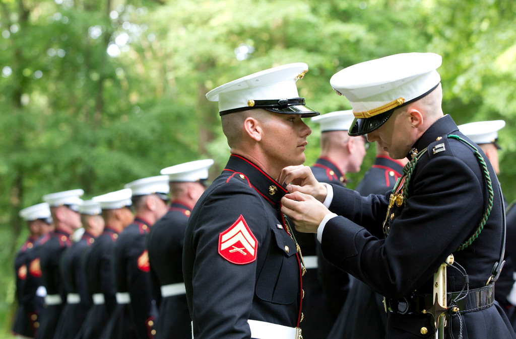 . A U.S. Marine Corps officer, right, helps an enlisted soldier adjust his tunic as they participate in a commemoration at the American Marine Memorial in Belleau Wood prior to a service at the Aisne-Marne American Cemetery in Belleau, France, Sunday, May 27, 2018. (AP Photo/Virginia Mayo)
