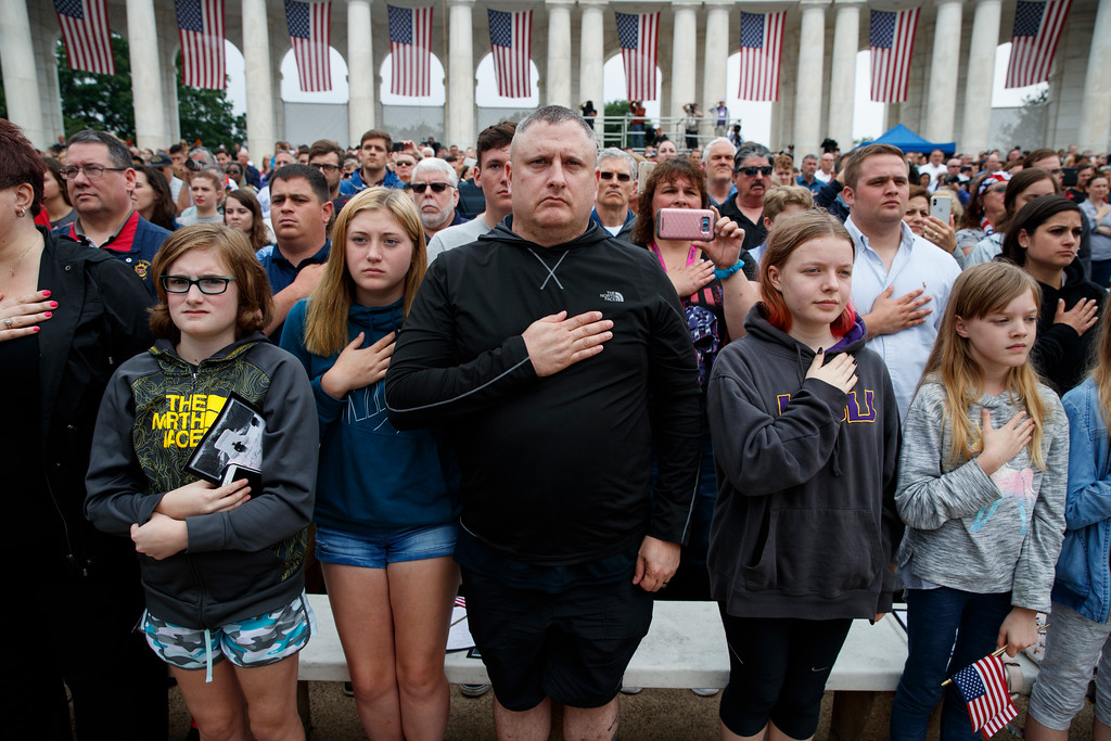 ". Audience members bow their heads as ""Taps\"" is played during a Memorial Day ceremony at Arlington National Cemetery, Monday, May 28, 2018, in Arlington, Va. (AP Photo/Evan Vucci)"