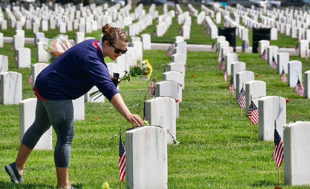 . Former Navy veteran Sarah Borquez places flowers at veterans\' grave stones during an observance for Memorial Day at the Los Angeles National Cemetery in Los Angeles on Monday, May 28, 2018. Californians are paying their respects on Memorial Day to those who have died serving their country. (AP Photo/Richard Vogel)