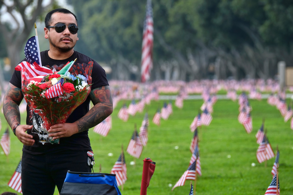 . Luis Canela, brings flowers to his uncles gravesite, during an observance for Memorial Day at the Los Angeles National Cemetery in Los Angeles on Monday, May 28, 2018. Californians are paying their respects on Memorial Day to those who have died serving their country. (AP Photo/Richard Vogel)