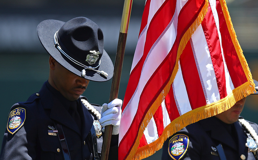 . A Union City, Calif., police officer bows his head while holding the colors during a moment of silence in honor of Memorial Day prior to the baseball game between the Oakland Athletics and the Tampa Bay Rays, Monday, May 28, 2018, in Oakland, Calif. (AP Photo/Ben Margot)