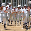 Kaneland players greet Madelyn Wheatley at home plate after a home run during regional championship action at Rosary in Aurora on Saturday, May 26.  Steve Bittinger - For Shaw Media