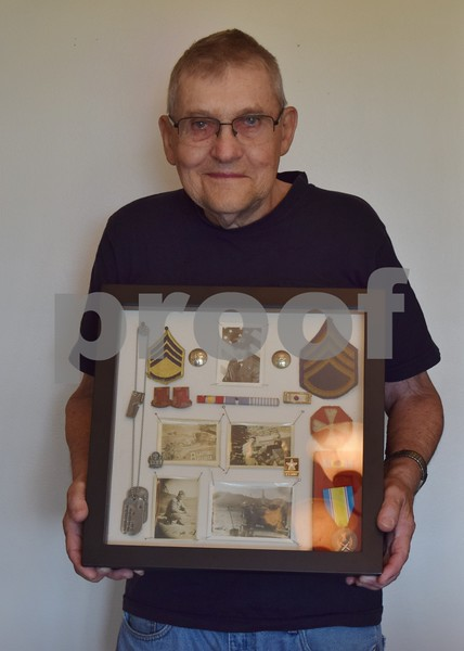Leslie Larson, 83, of Shabbona, holds items from his 16 months and two weeks he served in the U.S. Army in Korea during the Korean War. Items he has saved include his dog tags, photos and patches and buttons from his uniform.