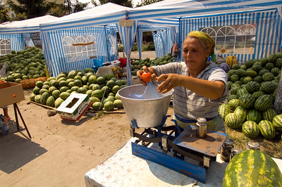 Lacal woman at her market stall selling water melons and other vegetables, Apuseni Mountains, Transylvania, Romania