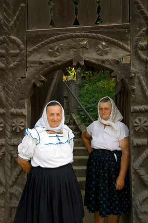 Local women by traditional wooden gate, Budesti, Maramures, Romania