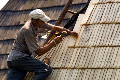 Man fixing his wooden roof, Maramures, Romania