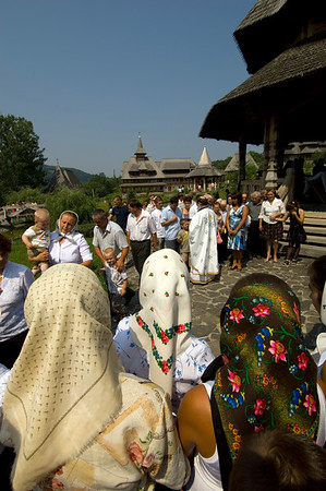 Worshippers dressed in traditional Maramures dress attend open air mass, and receive blessing from a priest, Barsana Monastery, Barsana, Maramures, Romania