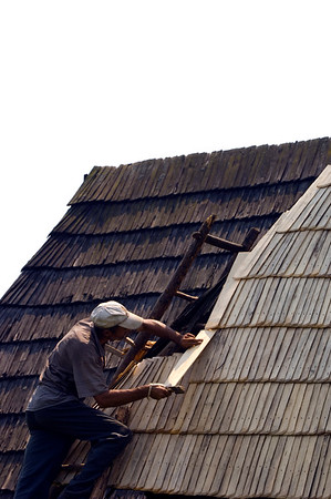 Man fixing his wooden roof, Maramures, Romania