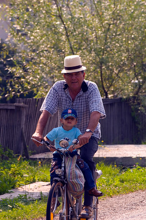 Man and his grandson on a bicycle, Maramures, Romania
