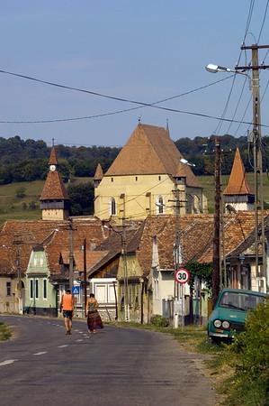 Citadel rising above rooftops of town, Biertan, Transylvania, Romania