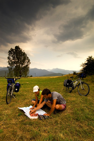 Girl and boy cyclists at the foot of Fagaras Mountains are resting and planning a journey ahead with a map, Fagaras Mountains, Transylvania, Romania
