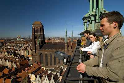 Young people admiring view of Old Town from viewing gallery of Old Town Hall  clock tower, Gdansk, Poland