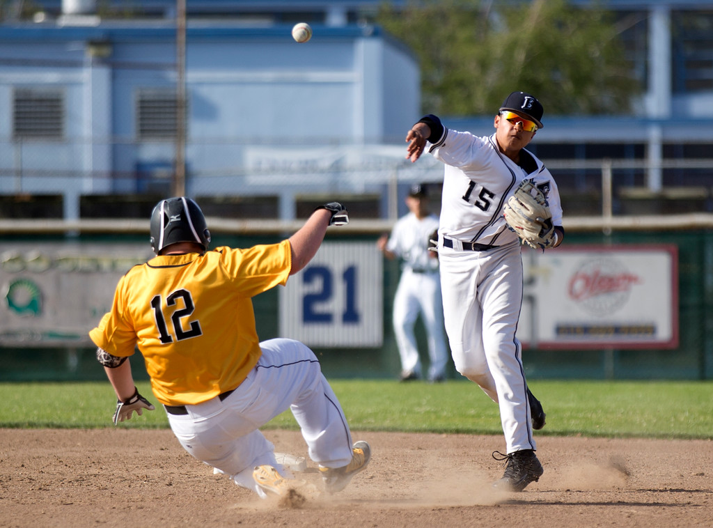 . Encinal shortstop Ricky Marquez throws over Bishop O\'Dowd\'s Ben Lancaster (12) to complete a double play during the fourth inning of a high school baseball game, Wednesday, April 20, 2016, in Alameda, Calif. O\'Dowd won, 7-4. (D. Ross Cameron/Bay Area News Group)