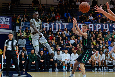 Moreau Catholic's Oscar Frayer (21) saves an out of bounds ball while playing Miramonte during the first period of their North Coast Section Division 3 boys basketball championship game at McKeon Pavilion in Moraga, Calif., on Saturday, March 5, 2016. (Jose Carlos Fajardo/Bay Area News Group)