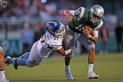 De La Salle quarterback Abel Ordaz (10) runs with the ball while being tackled by Serra's Caleb Tuimavave (27) in the first quarter of their game at De La Salle High School in Concord, Calif., on Friday, Sept. 2, 2016. (Jose Carlos Fajardo/Bay Area News Group)