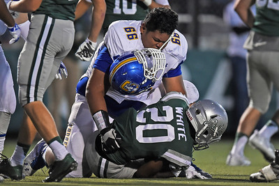 Serra's Atonio Mafi (66) loses his helmet after tackling De La Salle's Tre White (20) in the first quarter of their game at De La Salle High School in Concord, Calif., on Friday, Sept. 2, 2016. (Jose Carlos Fajardo/Bay Area News Group)