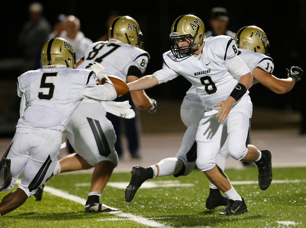 . Archbishop Mitty quarterback Trenton Scharrenberg (8) hands off to Kyle Evans (5) against Bellarmine College Prep in the first half of their WCAL football game Friday night, Nov. 8, 2013 at San Jose City College in San Jose, Calif. (Karl Mondon/Bay Area News Group)