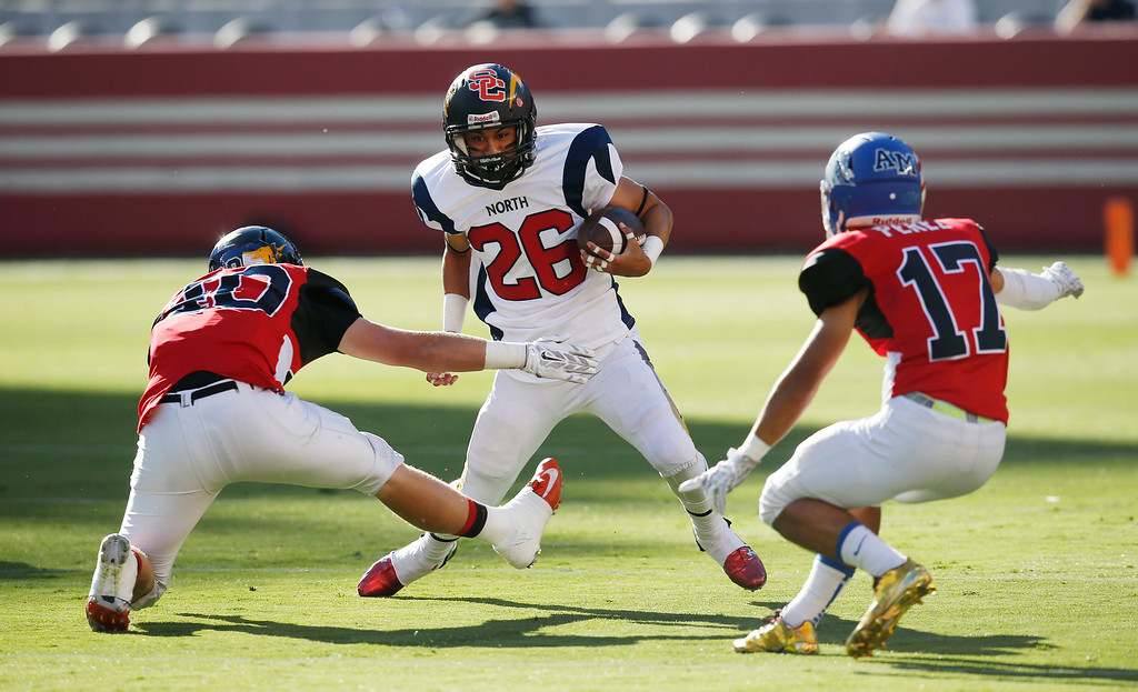 . North\'s Manu Turituri is surrounded by the South\'s Jake Holton, at left, and Nicholas Perez in the first quarter during the Charlie Wedemeyer high school all-star football game at Levi\'s Stadium in Santa Clara, Calif., on Saturday, July 16, 2016. (Jim Gensheimer/Bay Area News Group)