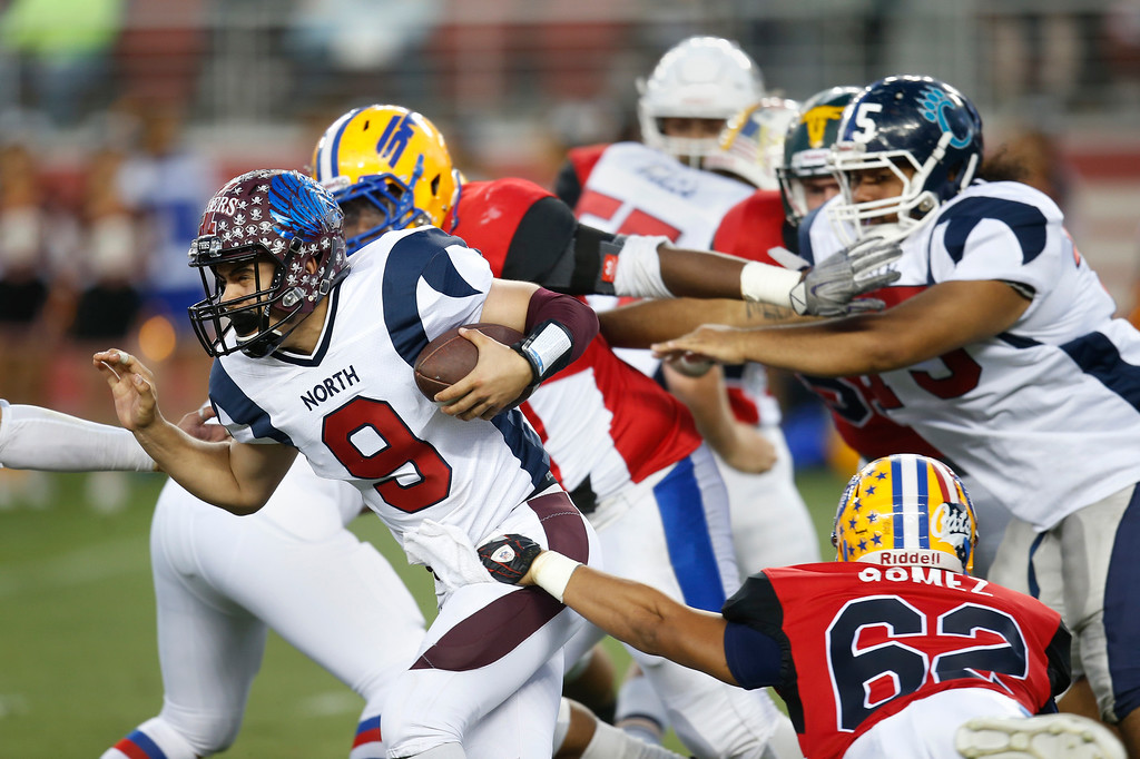 . North quarterback Marcus Romero breaks a tackle by South\'s Joel Gomez on a keeper in the fourth quarter during the Charlie Wedemeyer high school all-star football game at Levi\'s Stadium in Santa Clara, Calif., on Saturday, July 16, 2016. (Jim Gensheimer/Bay Area News Group)