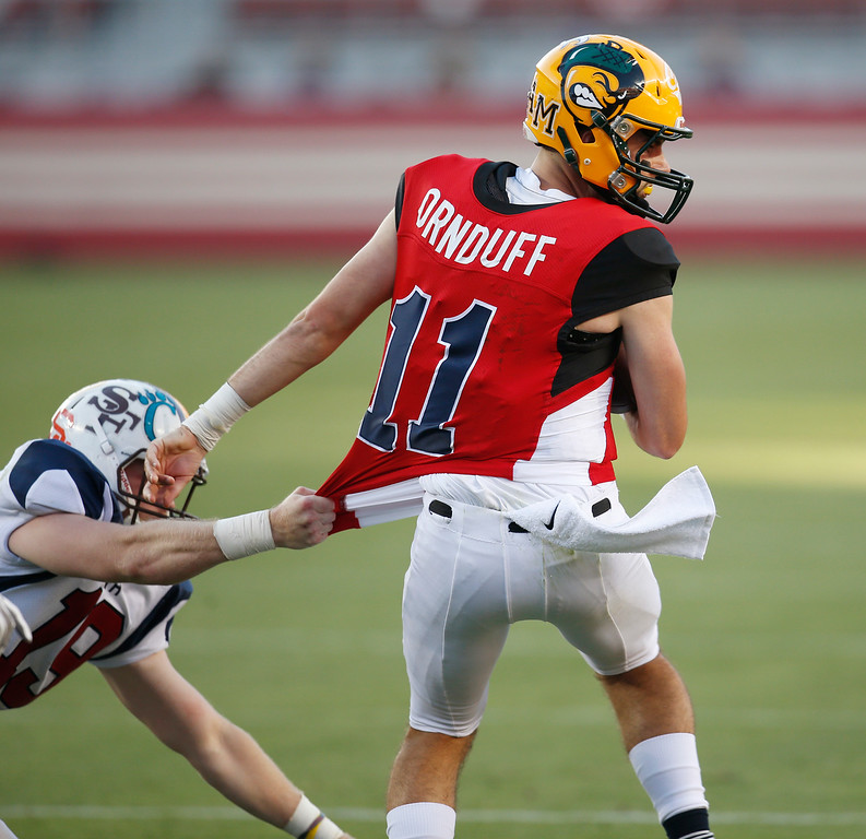 . North\'s Tommy MacDevitt grabs the jersey of South quarterback Erik Ornduff in the third quarter during the Charlie Wedemeyer high school all-star football game at Levi\'s Stadium in Santa Clara, Calif., on Saturday, July 16, 2016. (Jim Gensheimer/Bay Area News Group)
