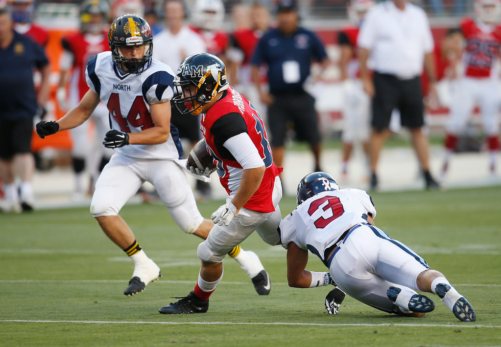 . South\'s James Rodriguez slips a tackle by North\'s Vincent Fernandez on a pass play in the third quarter during the Charlie Wedemeyer high school all-star football game at Levi\'s Stadium in Santa Clara, Calif., on Saturday, July 16, 2016. (Jim Gensheimer/Bay Area News Group)