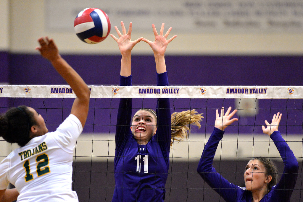 . From left, Castro Valley High\'s Marbella Daniel (12) gets her shot blocked by Amador Valley High\'s Summer Reeves (11) and Rachel Malmrose (9) during their non-conference game in Pleasanton, Calif., on Wednesday, Aug. 31, 2016. Castro Valley High went on to win the match in three straight sets. (Doug Duran/Bay Area News Group)