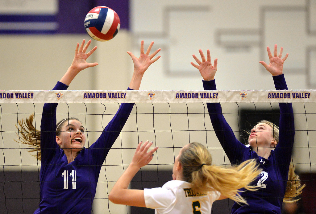 . Amador Valley High\'s Summer Reeves (11), left, and teammate Natalie Lambros (2), right, both try to block a shot by Castro Valley High\'s Kellie Jordan (6) during their non-conference game in Pleasanton, Calif., on Wednesday, Aug. 31, 2016. Castro Valley High went on to win the match in three straight sets. (Doug Duran/Bay Area News Group)