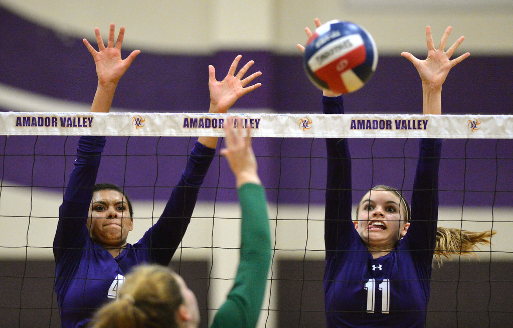 . Amador Valley High\'s Mahlia Jackson (4), left, and teammate Summer Reeves (11) try to block a shot during their non-conference game against Castro Valley High in Pleasanton, Calif., on Wednesday, Aug. 31, 2016. Castro Valley High went on to win the match in three straight sets. (Doug Duran/Bay Area News Group)