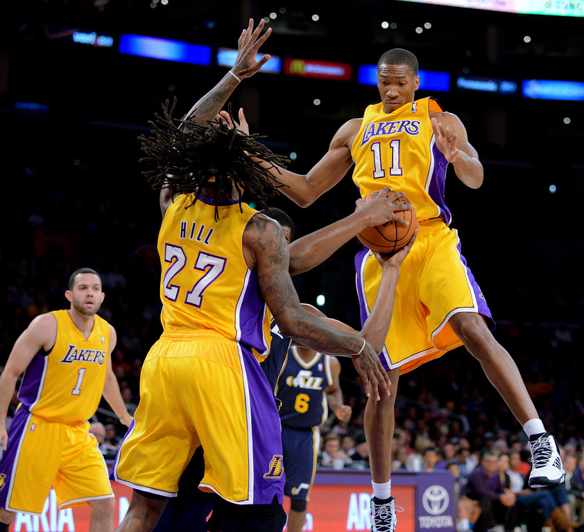 . Los Angeles Lakers\' Wesley Johnson (11) and Jordan Hill (27) guard  Utah Jazz\'s Derrick Favors in the NBA preseason basketball game at Staples Center in Los Angeles, CA. on Tuesday, October 22, 2013. (Photo by Sean Hiller/Daily News)